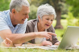 Smiling senior couple using laptop while lying at the park